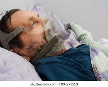 A sick man in an oxygen mask in a hospita