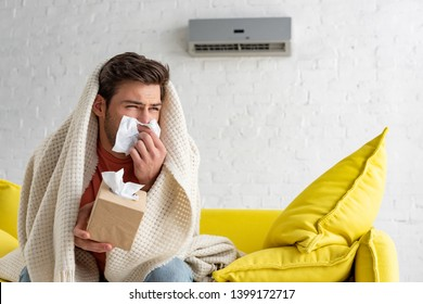sick man with paper napkins warming under blanket while sitting under air conditioner at home