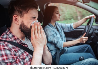 Sick man is riding in car. He is sneezing in napkin. Girl is driving car. She is looking straight forward.