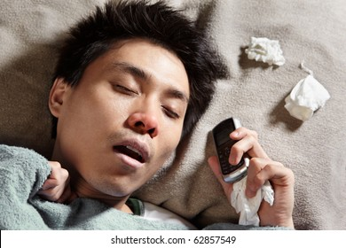 A sick man sleeping while holding his cell phone