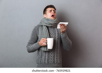 Sick Man in sweater and scarf sneezes while holding cup of tea over gray background