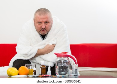Sick  man wearing pajama suffering cold and winter flu virus having medicine