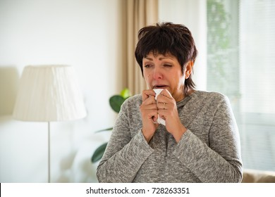 Sick mature woman catch cold. Sneezing with handkerchief, coughing, got flu, having runny nose.