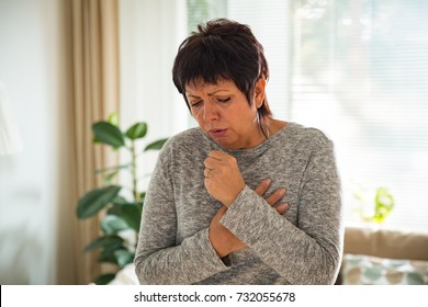 Sick mature woman with sore throat, standing in living room at home. Catching cold, having cough.