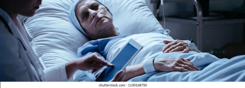 Sick, middle-aged woman looking sadly at her doctor who is checking a tablet