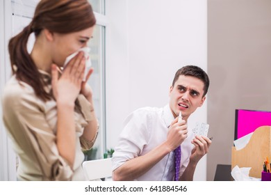Sick office worker stands near her colleague at the office and wipes nose