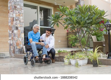 Sick Old man in a Wheelchair is Receiving a Help From a Young Doctor in Home Visit.