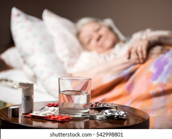 Sick old woman lying in bed at home. Focus on medicine and glass of water in foreground