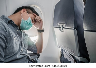 Sick on airplane, Young man wearing mask sitting in plane with headache and fever, A man holding head and feeling headache,  Sick passenger man sitting seat in airplane