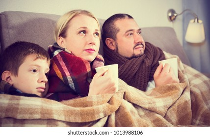 Sick parents and their son with scarf on neck lying on sofa under blanket