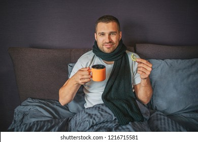 Sick but positive young man sits on bed in bedroom and looks on camer. He holds orange cup in one hand and piece of lemon in another one. Guy smiles. He looks happy.