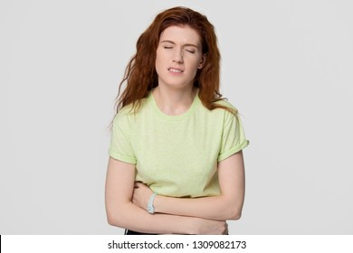 Sick redhead woman feel stomach abdomen ache holding belly, upset red-haired girl suffer from pain gastritis pancreatitis diarrhea symptom indigestion problem isolated on grey white studio background