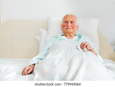 Sick and sad elderly woman laying in bed in the nursing home.