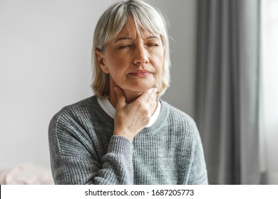 Sick senior adult elderly women touching the neck feeling unwell coughing with sore throat pain.Healthcare and medicine concept