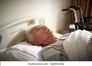 sick senior asian man lying in hospital bed appears to be sad and helpless