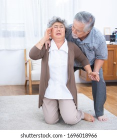 Sick senior asian woman with headache lying on the floor after falling down old man help her.