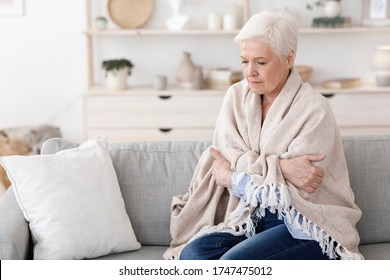 Sick senior lady sitting on couch covered with blanket, freezing shivering due to high temperature, suffering from coronavirus at home