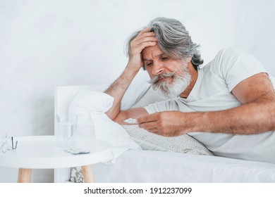 Sick senior stylish modern man with grey hair and beard indoors lying on the bed and feels bad.