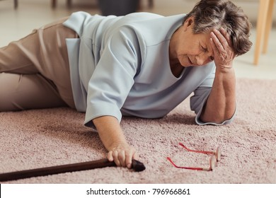 Sick senior woman with headache lying on the floor after falling down - Shutterstock ID 796966861