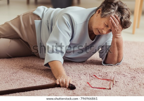 Sick senior woman with headache lying on the floor after falling down