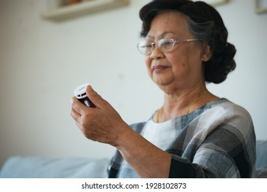 Sick senior woman hold pills bottle and read medicine prescription label and looking at medicine instructions side effects at home. Health and Medical concept.