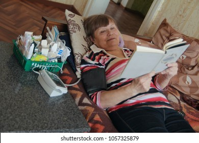 Sick senior woman reading at bed with tablets and device for measuring pressure