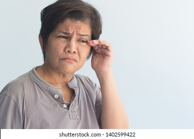 sick senior woman suffering from dry eye, eye irritation or inflammation