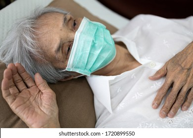Sick senior woman wear a mask lying in uncomfortable bed,unwell,exhausted old people have a fever,cold and flu,tired elderly patient with painful of disease,symptoms of Covid-19,Coronavirus infection
