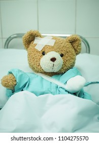A sick teddy bear with a bandage and plaster is lying in bed in hospital.