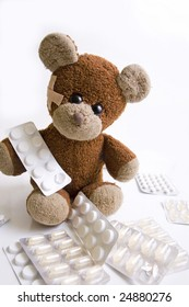 A sick teddy bear is sitting between pills. Adhesive bandage in his face.