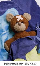 Sick teddy is lying in bed.