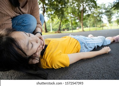 Sick teen daughter is fainted and fallen on floor while playing at park,asian mother help,take care,child girl with congestive heart failure,female unconscious lying down on ground suffer heart attack