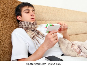 Sick Teenager with the Box with a Pills on the Sofa at the Home