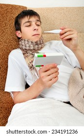 Sick Teenager with Thermometer and Drug on the Sofa at the Home