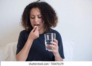 Sick and tired black woman taking medicine pill