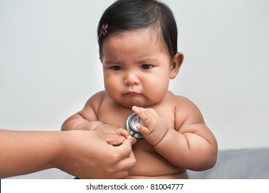 Sick and upset baby girl getting a medical check up by doctor