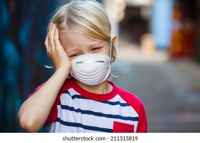 A sick upset boy with a headache is wearing a protective face mask.