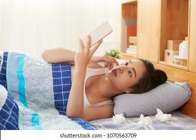 Sick Vietnamese woman lying in bed and reading news in her phone