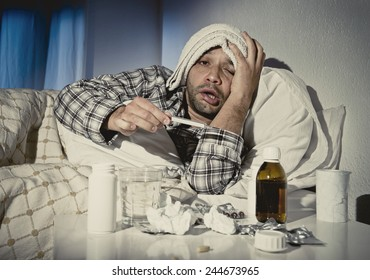 sick wasted man lying in bed wearing pajama suffering cold and winter flu virus having medicine tablets in health care concept looking temperature on thermometer