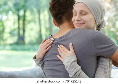 Sick wife hugging husband after successful therapy against brain cancer