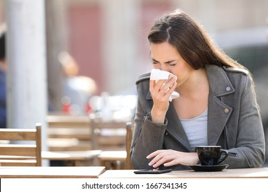 Sick woman blowing her nose with tissue sitting on a coffee shop terrace