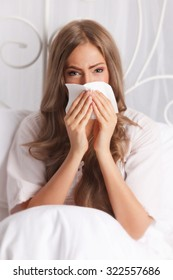 Sick woman blowing her nose in the bed