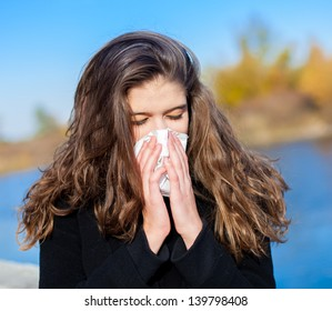 Sick woman with a cold blowing into tissue, outdoor