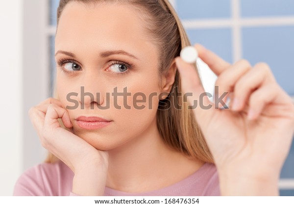 Sick woman. Depressed young woman holding a pill and looking at it