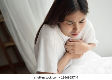 sick woman with heart attack or breast cancer; portrait of woman suffering from heart attack, chest pain, breast cancer; woman health care concept; asian middle east 20s young adult woman model
