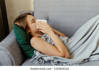The sick woman, holding a handkerchief, sneezing and feeling freezing, lying on the bed, at home. Health problem.