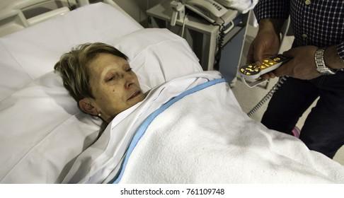 Sick woman lying in hospital bed, virus and disease
