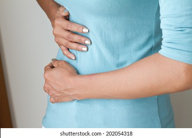 sick woman with menstruation pain, ill woman suffers from cramp, stomach ache, belly pain, hand holding belly closeup; woman menstrual pain, period cramp, stomachache, gastritis, reflux pain concept