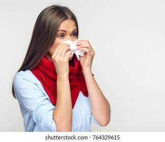 Sick woman with red scarf using tissue. Isolated portrait.
