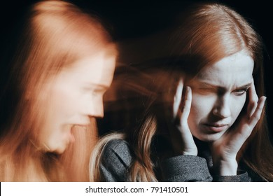 Sick woman with schizophrenia hearing voices. Blurred face on black background.